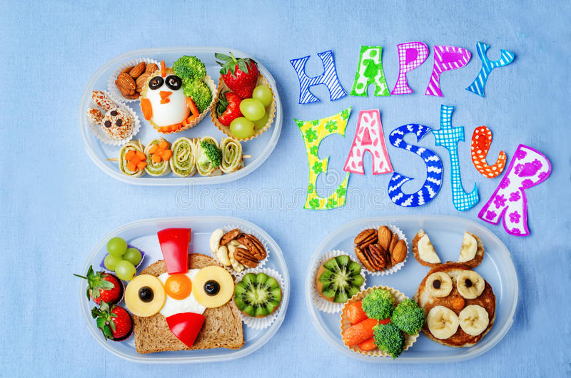 Happy Easter words with school lunch boxes for kids with food in. The form of funny faces. the toning. selective focus royalty free stock photo