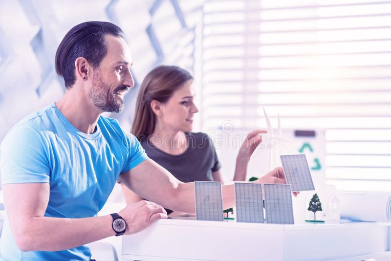 Happy eco engineer smiling white placing little solar batteries stock image