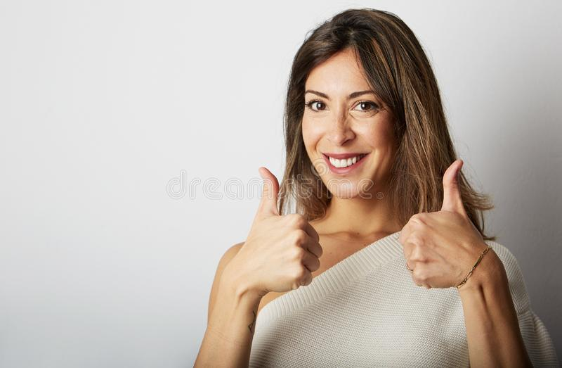 Happy ecstatic young brunette woman with long hair totally agrees over empty white background.Girl showing ok sign and stock images