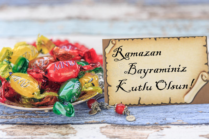 Happy eid al fitr in turkish on the card with candies on vintage royalty free stock photo