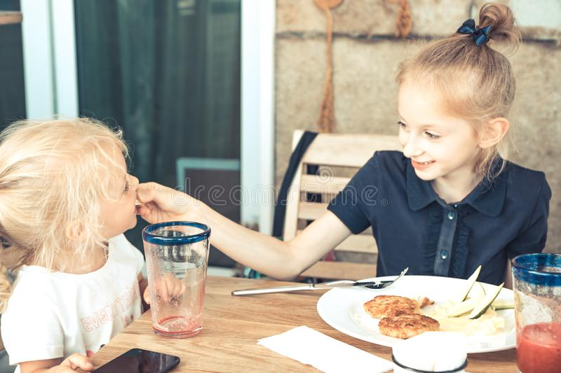 Happy elder sister feeding small sister in cafe restaurant concept children care childhood lifestyle royalty free stock photos