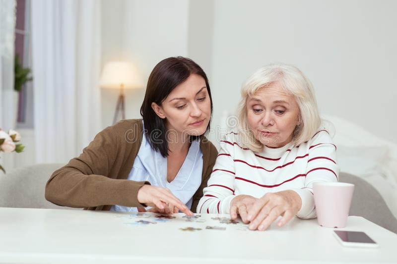 Happy elder woman and caregiver collecting puzzle. Pleasant time spending. Jolly elder woman and caregiver sitting while gathering puzzle stock images