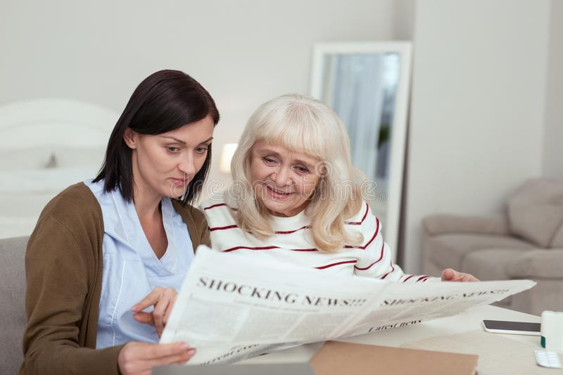 Happy elder woman and caregiver studying newspaper. Great news. Joyful elder women and caregiver reading news and looking down stock photo