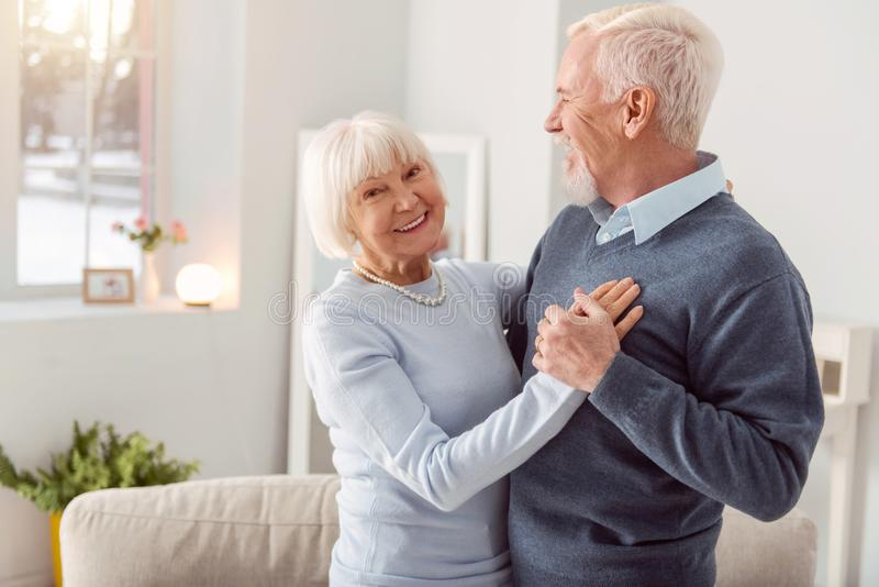 Happy elderly couple dancing waltz and smiling. Enjoy dancing. Happy charming elderly women smiling at the camera while dancing waltz with her husband in the royalty free stock images