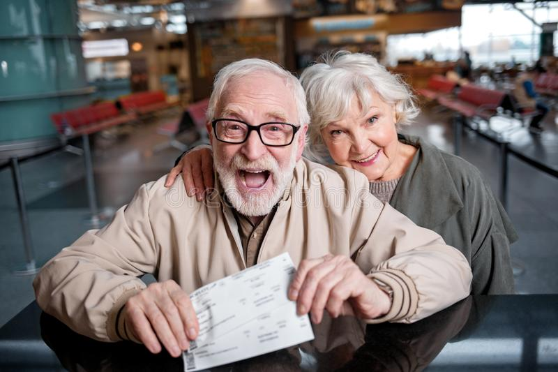 Happy elderly couple are demonstrating their boarding passes with gladness royalty free stock image