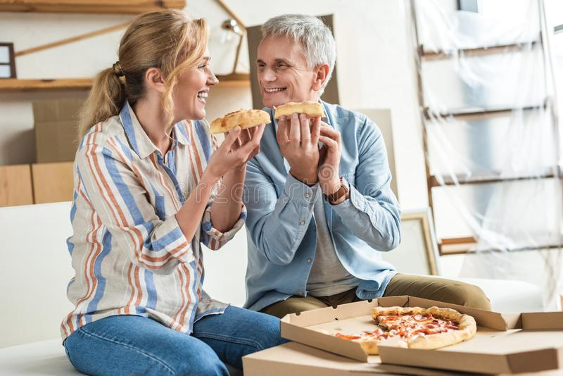 happy elderly couple eating pizza and smiling each other during relocation stock image