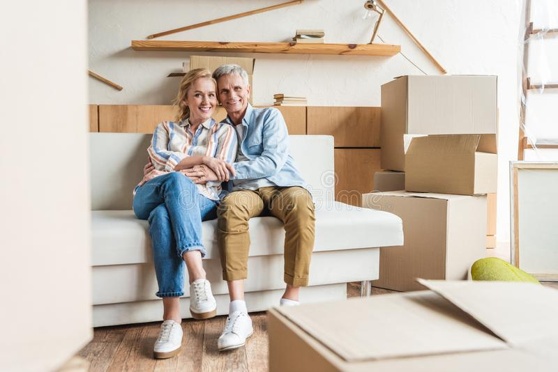 happy elderly couple embracing and smiling at camera while sitting together on couch in new house royalty free stock image