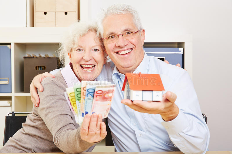 Happy elderly couple with Euro. Happy elderly couple with fan of Euro money and little house in their hands stock photos