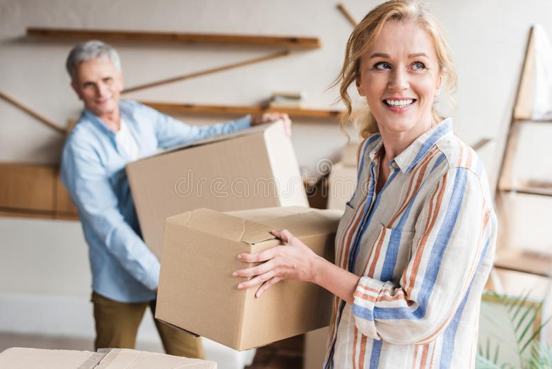 happy elderly couple holding cardboard boxes while moving royalty free stock photography