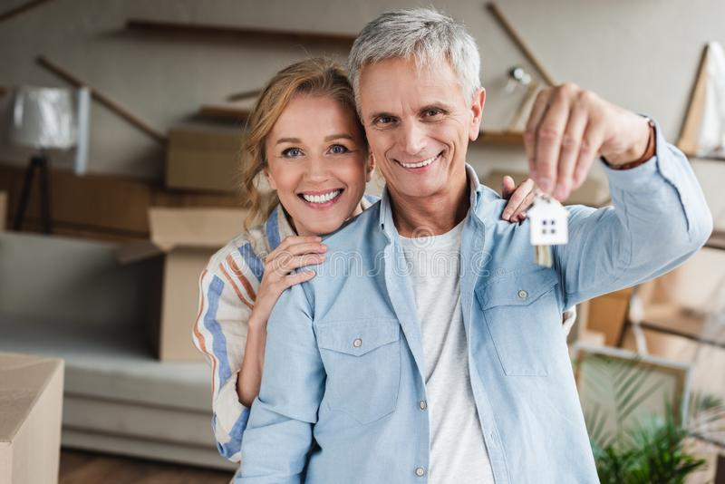 happy elderly couple holding keys from new house and smiling royalty free stock photography
