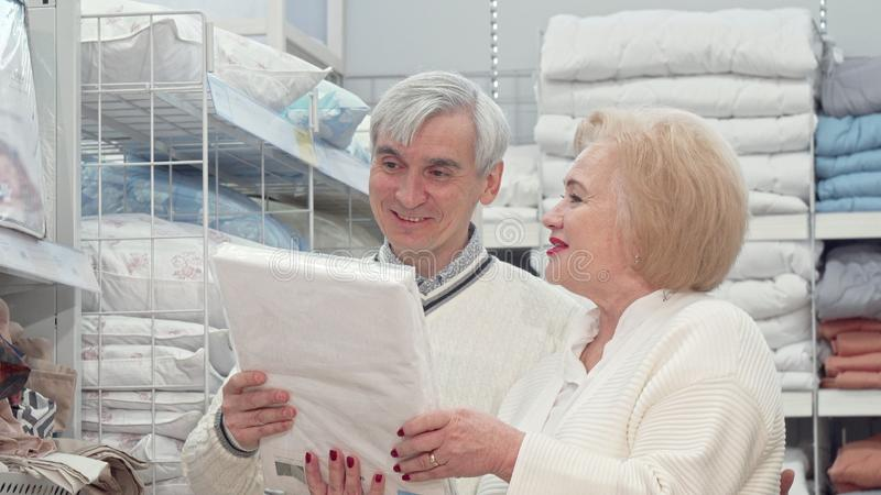 Happy elderly couple laughing, talking while shopping for home goods. Senior husband and wife enjoying shopping together at furnishings store. Retirement royalty free stock photos
