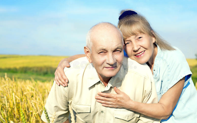 Happy elderly couple outdoor. Happy smiling couple: 68 year old men and 65 year old women outdoor at the wheat field royalty free stock photography