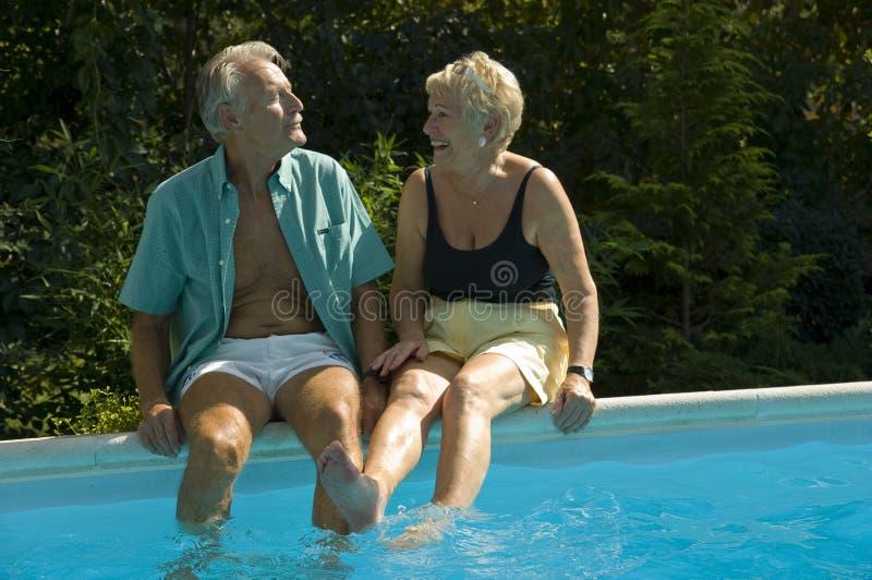 Happy elderly couple on pool royalty free stock photos