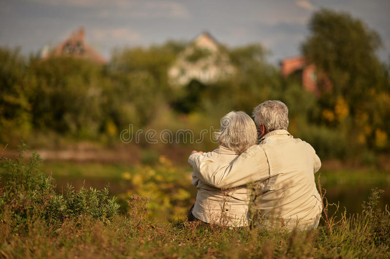 Happy elderly couple sitting embracing in autumn park royalty free stock photography