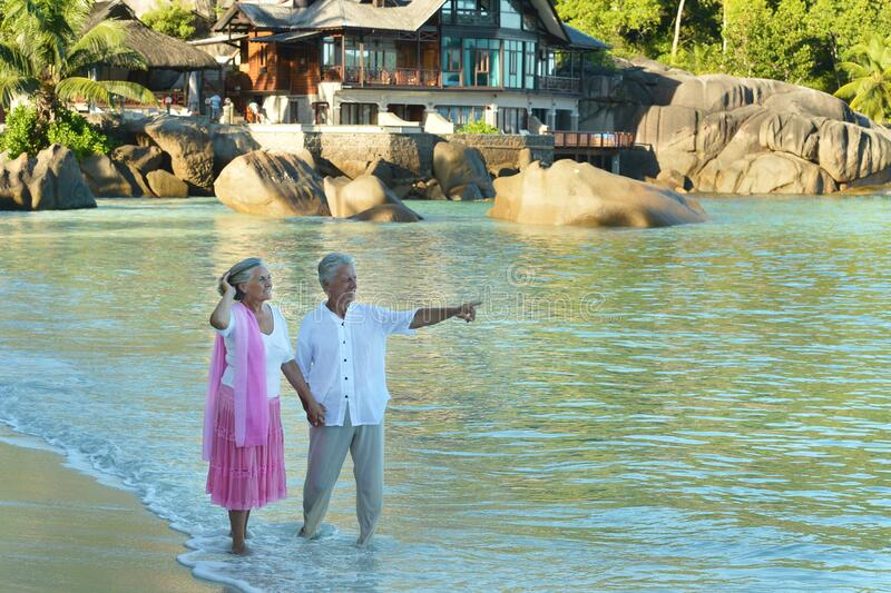 Happy elderly couple on tropical beach. man showing spmething stock photo