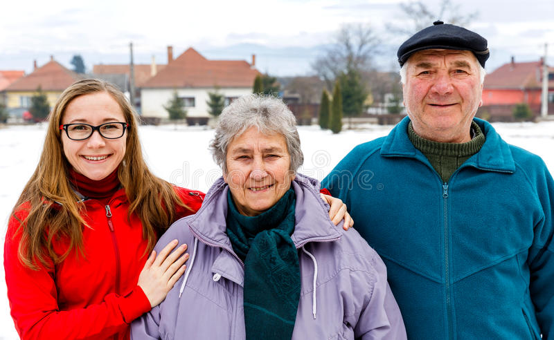 Happy elderly couple and young caregiver. Photo of happy elderly couple and young caregiver stock photography