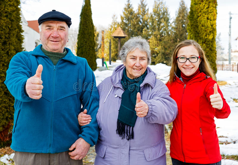 Elderly couple and young caregiver. Happy elderly couple and young caregiver showing thumbs up royalty free stock image