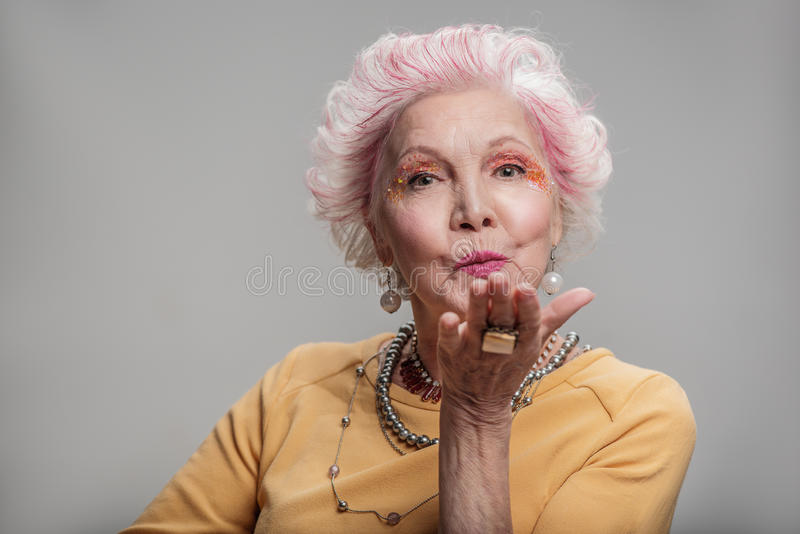 Happy elderly female posing with bright make-up royalty free stock images