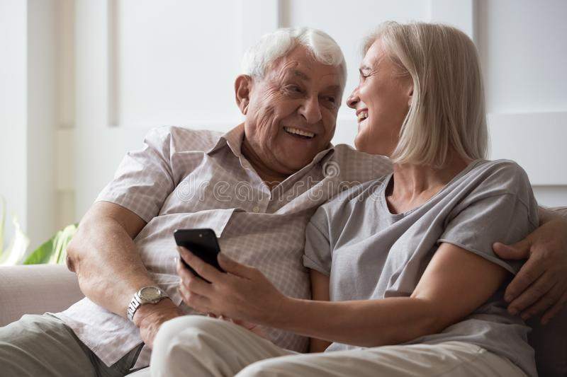 Elderly husband and middle-aged wife having fun using smartphone. Happy elderly husband and middle-aged wife have fun use smartphone new cool app, adult 50s stock images