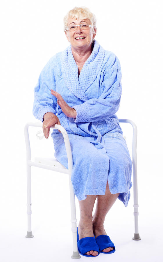 Happy elderly lady on shower seat. Elderly lady dressed in blue bath coat is sitting with happy smiling expression in face on shower seat with armrests for stock photography