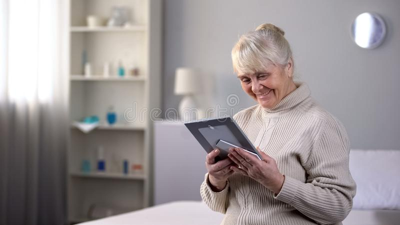 Happy elderly lady sitting alone and looking at photo, pleasant family memories royalty free stock images