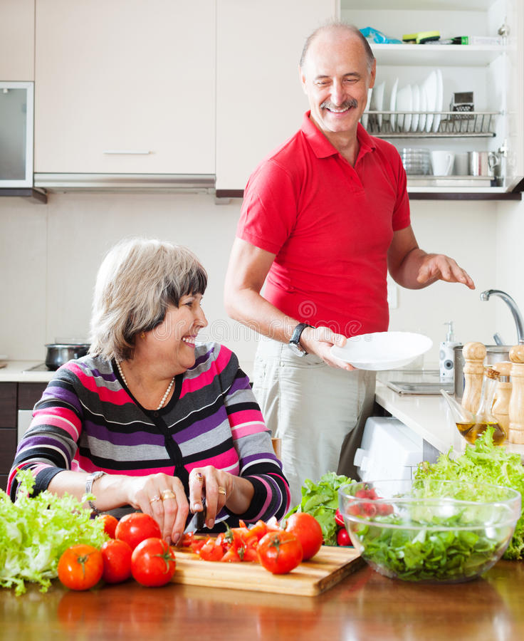 Happy elderly man and mature woman doing chores royalty free stock photography