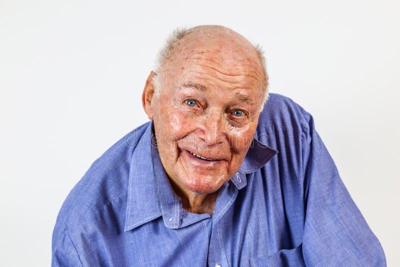 Happy elderly man sitting in a chair. Happy elderly man sitting in front of a white background stock photo
