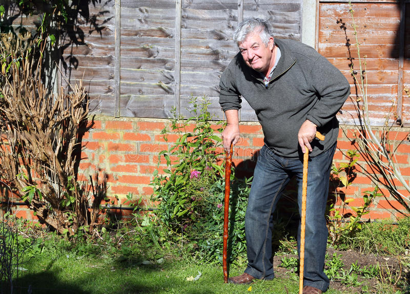 Happy elderly man with two walking sticks. A senior man having difficulty to walk using two walking sticks and smiling stock photography