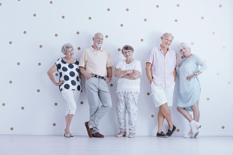 Happy elderly people in casual clothes in white studio with gold stock images