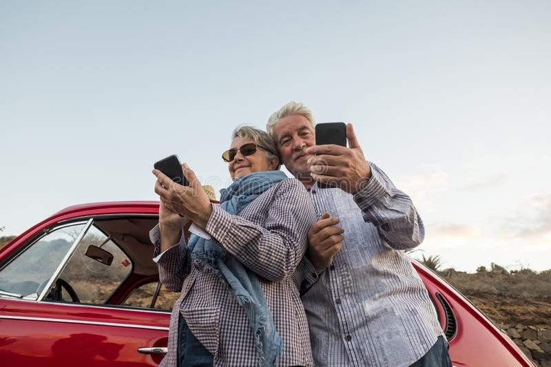 Happy elderly senior couple use mobile phones outdoor near a red beautiful retro car. leisure activity and travel together forever. Concept. modern use of royalty free stock photo