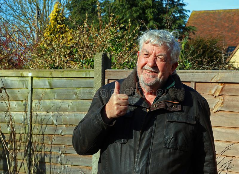 Happy contented senior man. Thumbs up. A happy elderly or senior man smiling and looking towards the camera.. Content. Thumbs up sign that all is well with him stock photo