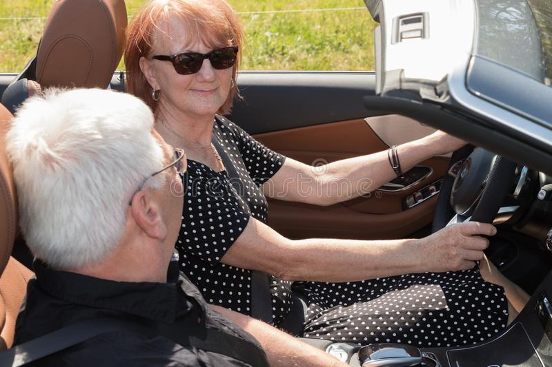 Happy elderly seniors couple with the car. Two happy elderly people drives with a luxury convertible car on a sunny day royalty free stock images