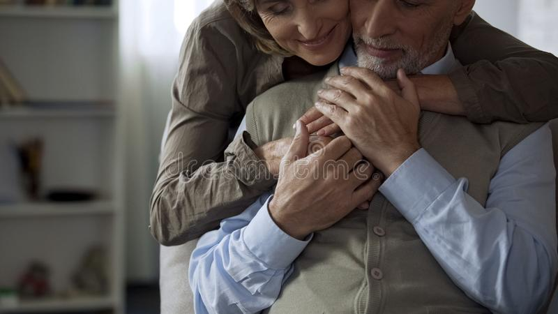 Happy elderly wife hugging husband, man holding her hands, harmonic relations stock photo
