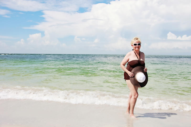 Happy elderly woman on beach stock photography
