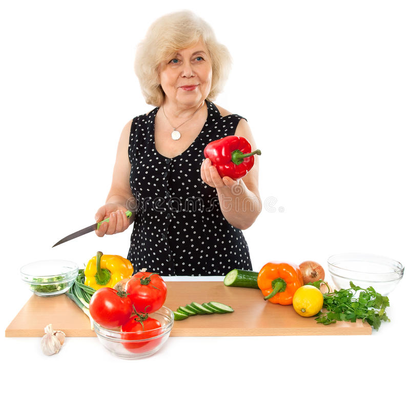Happy elderly woman cooking food royalty free stock photography