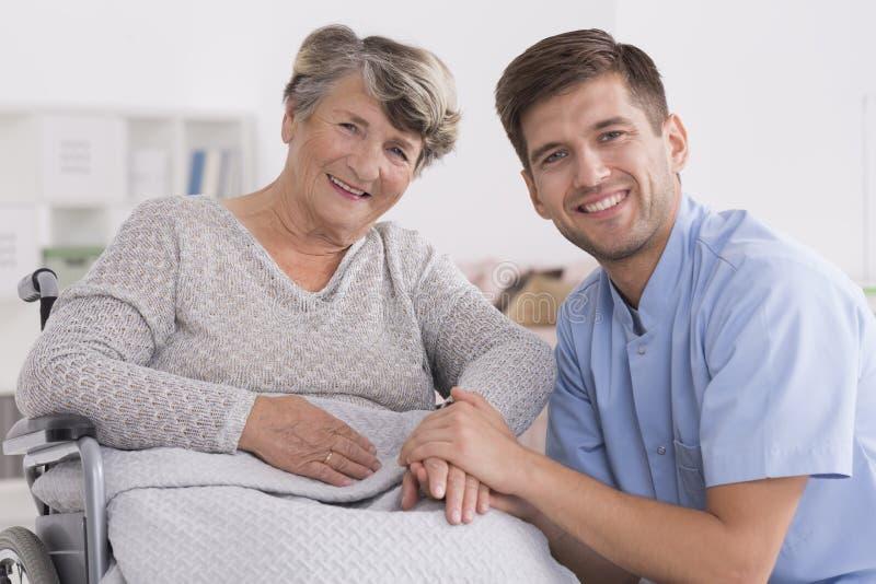 Happy elderly woman with male nurse. Happy elderly women with male nurse in retirement home stock image
