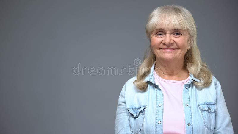 Happy elderly woman posing on camera, satisfied with pension, secure old age stock image