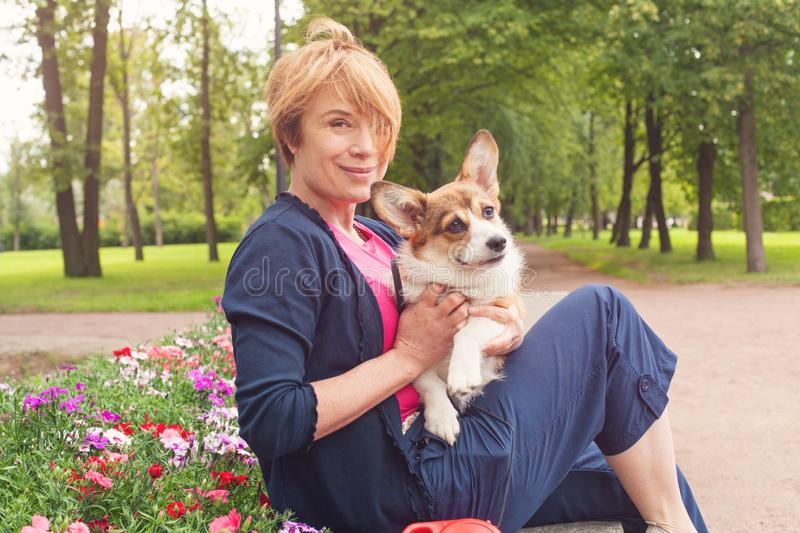 Happy elderly woman sitting with dog on bench in blossom summer park stock photo