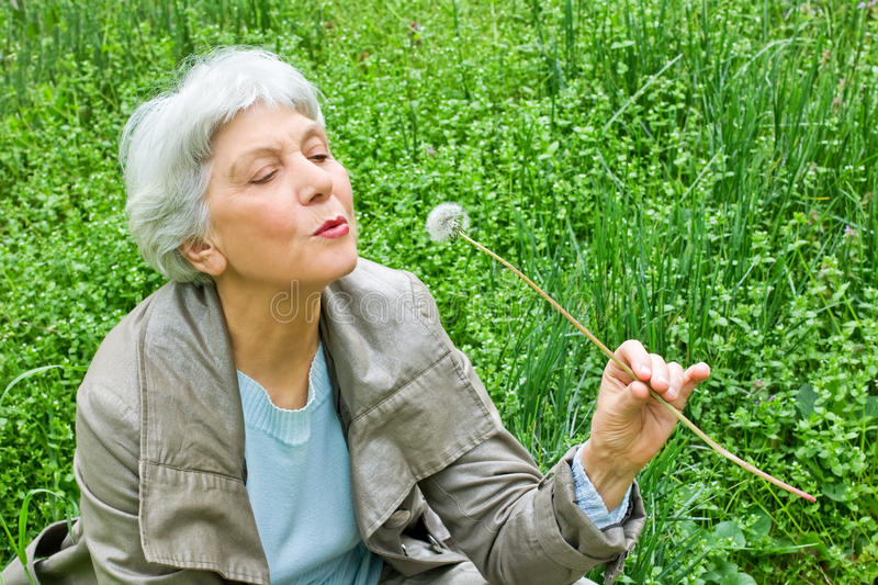Happy elderly woman sitting on a meadow blowing on a dandelion royalty free stock photo