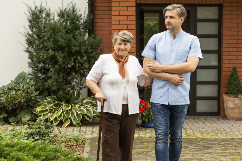 Happy  woman with walking stick and friendly caregiver in front of house. Happy elderly woman with walking stick and friendly caregiver in front of house royalty free stock photography