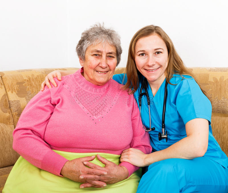 Happy elderly woman and young caregiver. Photo of elderly women and young caregiver royalty free stock image