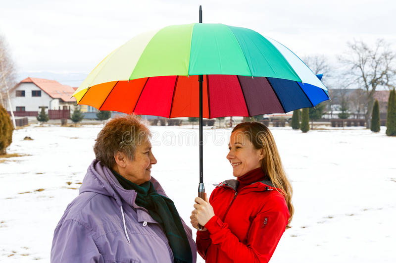 Happy elderly woman and young caregiver. Happy elderly women and young caregiver walking in the park with colorful umbrella stock image