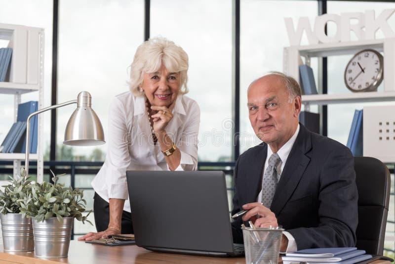 Happy elders in the office stock photos