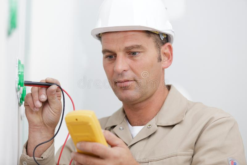 Happy electrician checking voltage in electrical wall socket stock photo
