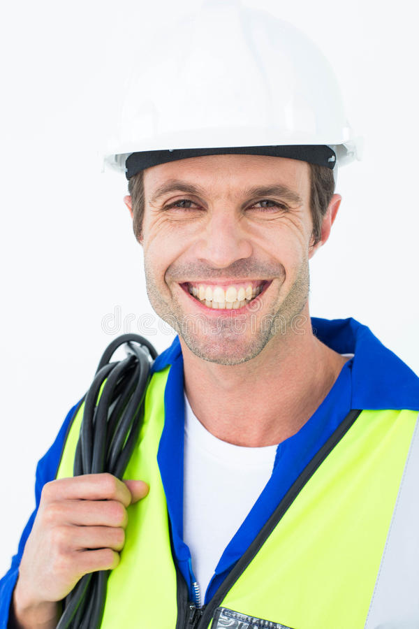 Happy electrician with wire against white background stock photography