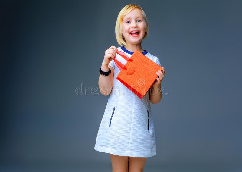 Happy elegant child on grey showing red christmas shopping bag stock photos