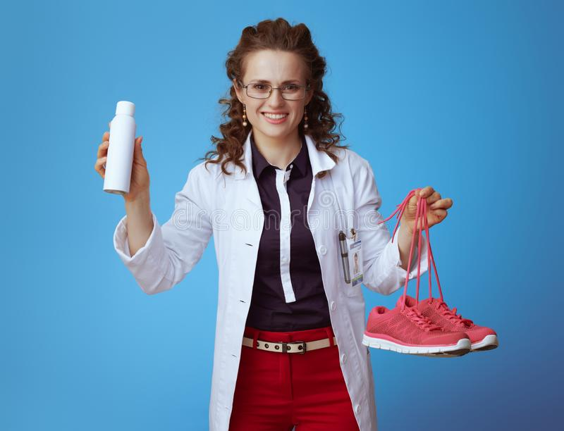 Doctor woman showing fitness sneakers and shoe deodorizer spray. Happy elegant doctor woman in bue shirt, red pants and white medical robe showing fitness stock photos