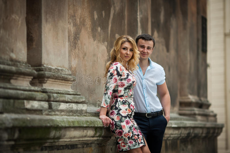Happy elegant dressed couple posing near old church stock photography