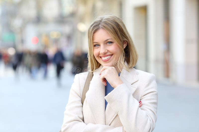 Happy elegant lady posing in the street. Front view portrait of a happy elegant lady posing looking at camera in the street royalty free stock photography