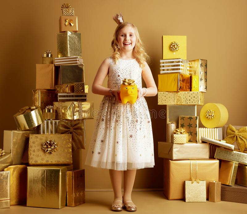 Happy elegant little princess with yellow piggybank with bow stock image